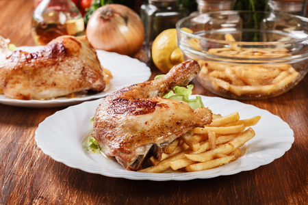 Roasted chicken legs with french fries and lettuce on a plate