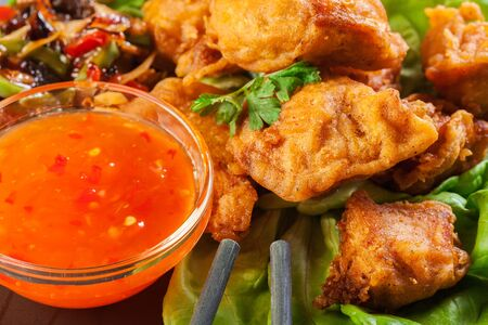 Fried chicken pieces in batter with sweet and sour sauce