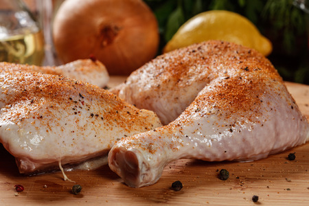 drumsticks: Raw chicken drumsticks seasoned with herbs on a chopping board