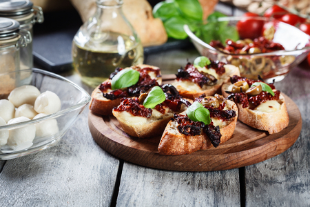 sundried: Appetizer bruschetta with sun-dried tomatoes, olives and mozarella. Italian cuisine Stock Photo