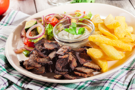 Grilled meat with French fries and fresh vegetables on a plate