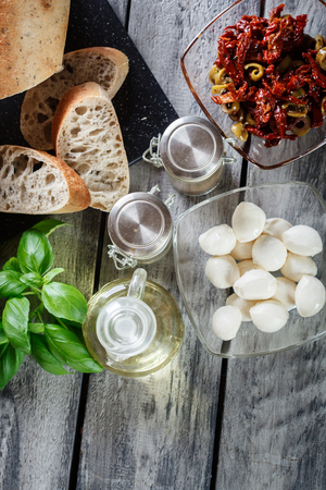 sundried: Ingredients ready for preparing bruschetta with sun-dried tomatoes, olives and cheese. Italian cuisine. Top view