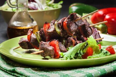 marinade: Grilled beef meat and vegetable kebabs on the green plate Stock Photo