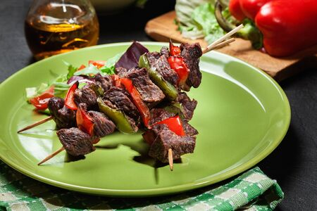 Grilled beef meat and vegetable kebabs on the green plate Stock Photo