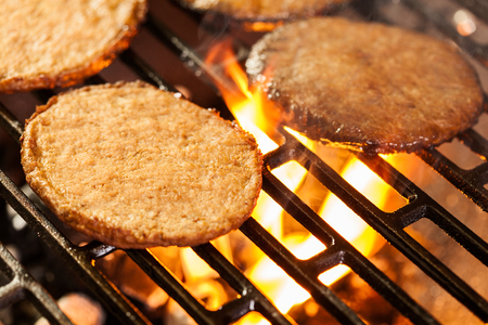 under fire: Hamburger patties on a grill with fire under. Selective focus