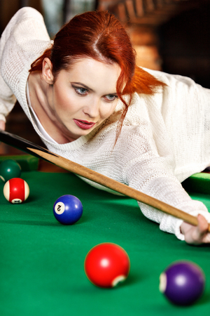 Young attractive woman plays the game of snooker pool table