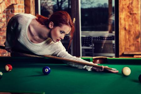 Jeune femme séduisante joue le jeu de table de billard billard. Concept d'amusement et de compétition. Image tonique