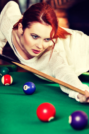 Young attractive woman plays the game of snooker pool table. Fun and competition concept. Toned image