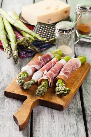 Prosciutto wrapped green asparagus on a cutting board Stock Photo