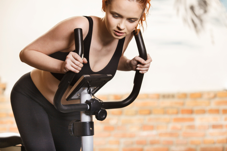 Active young woman doing exercise on bicycle at home. Fitness and weight loss concept.