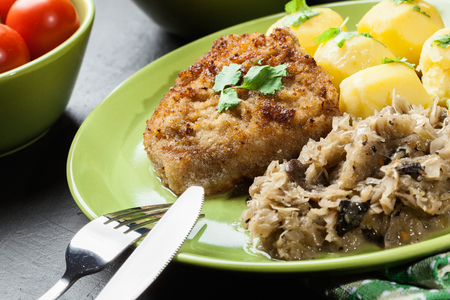 Fried pork schnitzel served with boiled potatoes and fried sauerkraut on a plate