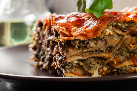 Piece of tasty hot lasagna with spinach on a plate. Italian cuisine.