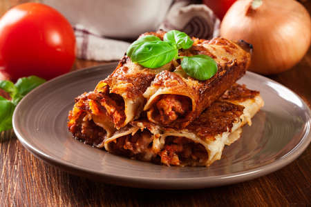 Baked cannelloni with minced meat and bechamel sauce on a plate. Italian cuisine Фото со стока