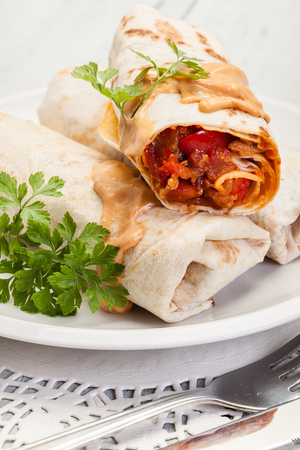 green bean: Mexican burritos wraps with mincemeat, beans and vegetables on a plate