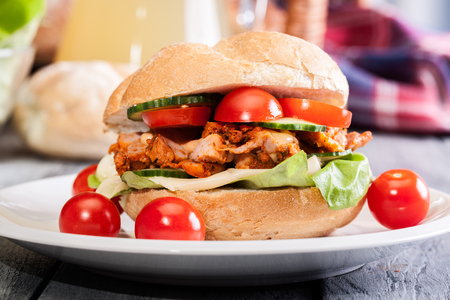 Kebab sandwich - fried chicken meat with cheese and vegetables in bun