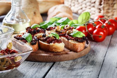 Voorgerechtbruschetta met in de zon gedroogde tomaten, olijven en mozarella. Italiaanse keuken