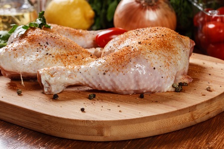 flesh eating animal: Raw chicken drumsticks seasoned with herbs on a chopping board