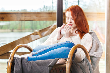 energizing: Atractive red-haired woman drinking cup of coffee sitting on Rocking chair. Young girl with hot energizing beverage. Calm and coziness.