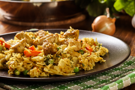 Fried rice nasi goreng with chicken and vegetables on a plate. Indonesian cuisine.