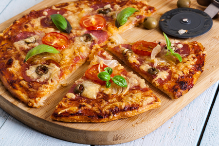 smack: Slices of pizza with bacon, olives and tomatoes on cutting board. Stock Photo