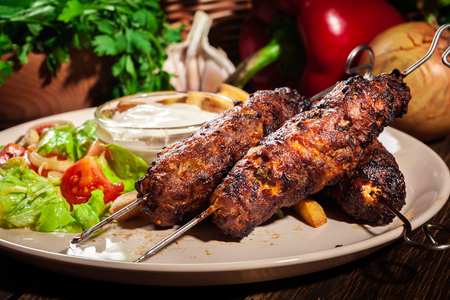 Grilled shish kebab served with fried chips and fresh salad