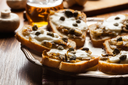 cutting: Crostini with fried mushrooms, onion and mozzarella cheese on a plate