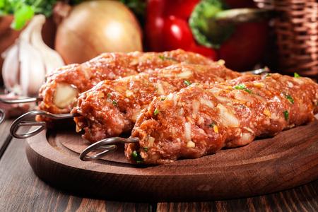 cutting: Raw traditional sish kebab on wooden cutting board