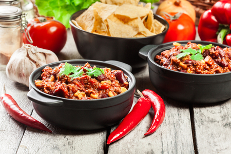 Bowls of hot chili con carne with ground beef, beans, tomatoes and corn. Mexican cuisine.