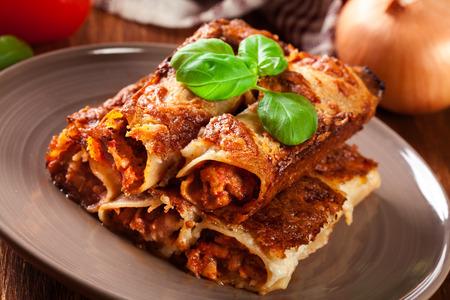 ミンチ肉と皿の上のベシャメル ソース焼きのカネロニ。イタリア料理 写真素材 - 83314699