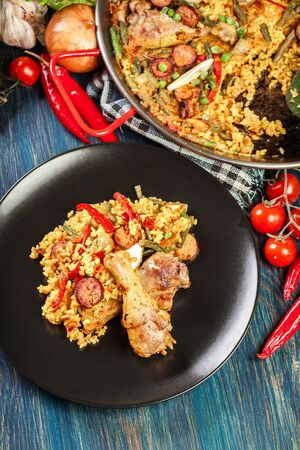 Traditional paella with chicken legs, sausage chorizo and vegetables served on black plate. Spanish cuisine. Top view Stock Photo