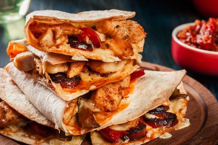 Stapel quesadilla's met kip, worstchorizo en rode peper die met salsa wordt gediend. Mexicaanse keuken. Zijaanzicht