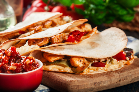Mexican Quesadilla with chicken, sausage chorizo and red pepper served with salsa.Side view