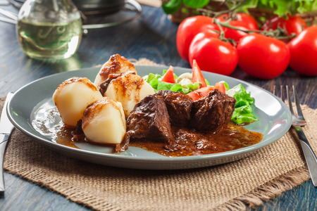 Pork meat stew served with potatoes and vegetable salad on a plate. Side view. Stock Photo