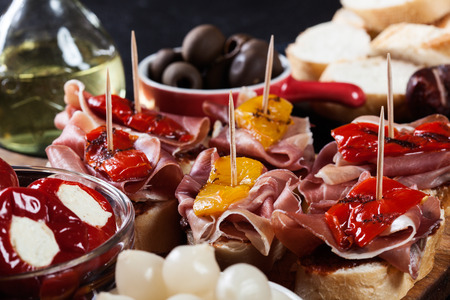 Spanish tapas with slices jamon serrano and grilled pepper. Also olives, salami, pickled onions, and peppers stuffed with cheese. Spanish cuisine Stock Photo