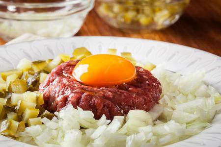 Steak tartar con la yema de huevo, cebolla y pepinillos en un plato Foto de archivo - 88759285