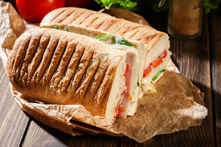 Toasted panini with ham, cheese and arugula sandwich on a paper
