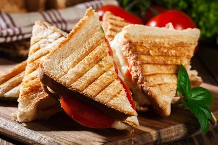 Stapel panini met ham, kaas en sla sandwich op een snijplank