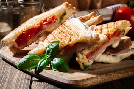 Pile de panini avec sandwich jambon, fromage et laitue sur une planche à découper Banque d'images - 88759331