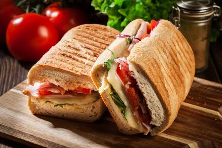 まな板の上のハム、チーズとルッコラのサンドイッチ トースト パニーニ