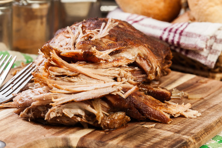 Slow cooked pulled pork shoulder on chopping board.