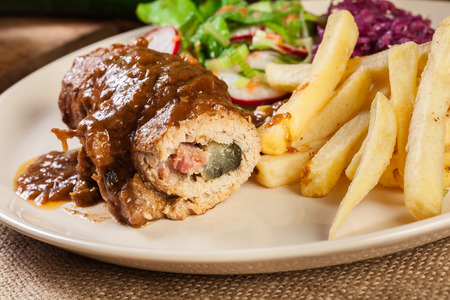 desk: Pork roulade with french fries with salad on a plate