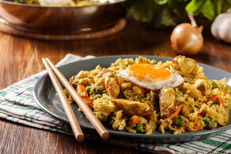 Fried rice nasi goreng with chicken egg and vegetables on a plate. Indonesian cuisine. Stock Photo