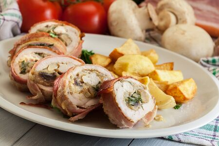 Chicken breast stuffed with champignon, onion and cheese wrapped with bacon served with baked potatoes Stock fotó