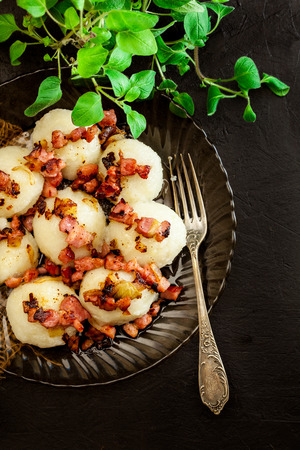 Potato dumplings stuffed with meat served with bacon on a plate. Top view