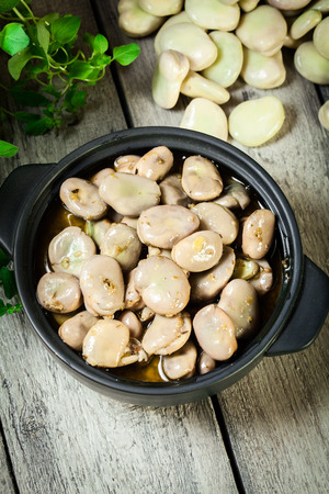 Broad beans stewed with onion and oregano on the wooden table. Sicilian cuisine. Top view