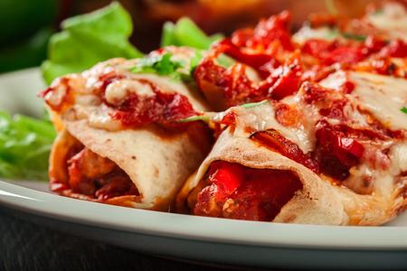 伝統的なメキシコのエンチラーダに鶏肉、スパイシーなトマトソース、チーズをプレートに盛り付けます。メキシコ料理 写真素材