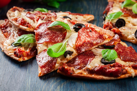 Slices of pizza pepperoni with olives served on a wooden table
