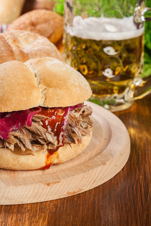 Pulled pork sandwich with red cabbage and bbq sauce on cutting board