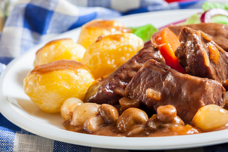 Beef Bourguignon stew served with baked potatoes on a plate. French cuisine