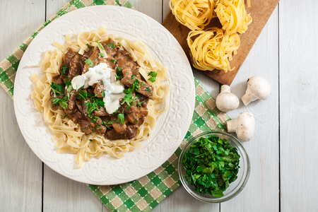 Homemade beef Stroganoff with mushrooms and tagliatelle pasta. Top view Reklamní fotografie